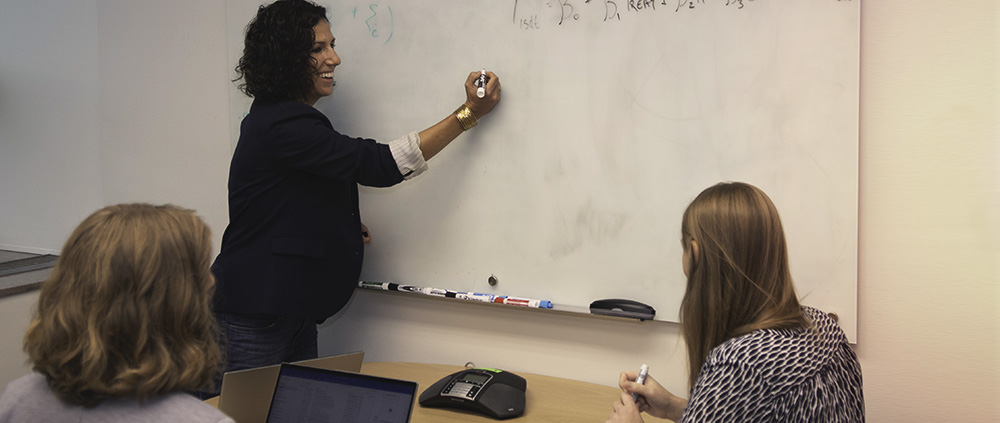 Woman writing in classroom white board