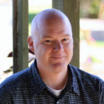 This is a headshot of Ron Houtman. He has light skin and is bald. He is looking at the camera and smiling. He is wearing a dark blue button down shirt. The background is foliage that is out of focus.