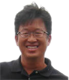 This is a headshot of David Wong. David has short, dark brown hair, medium skin, and wears glasses. He is smiling at the camera. He is wearing a dark brown collared shirt. The background is plain white.