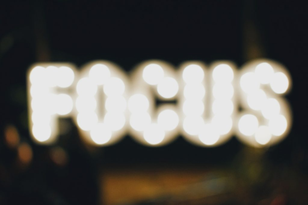"This is a picture of the word ""focus"" illuminated. The word focus appears out of focus and blurry."