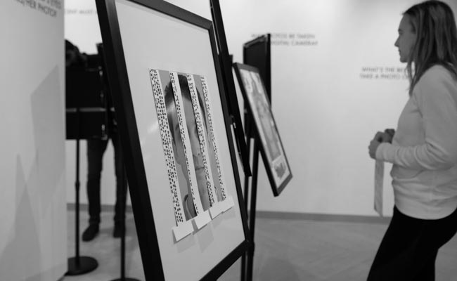 """A student examines art at the """"Do You Have Anything to Declare?"""" photo exhibit."""